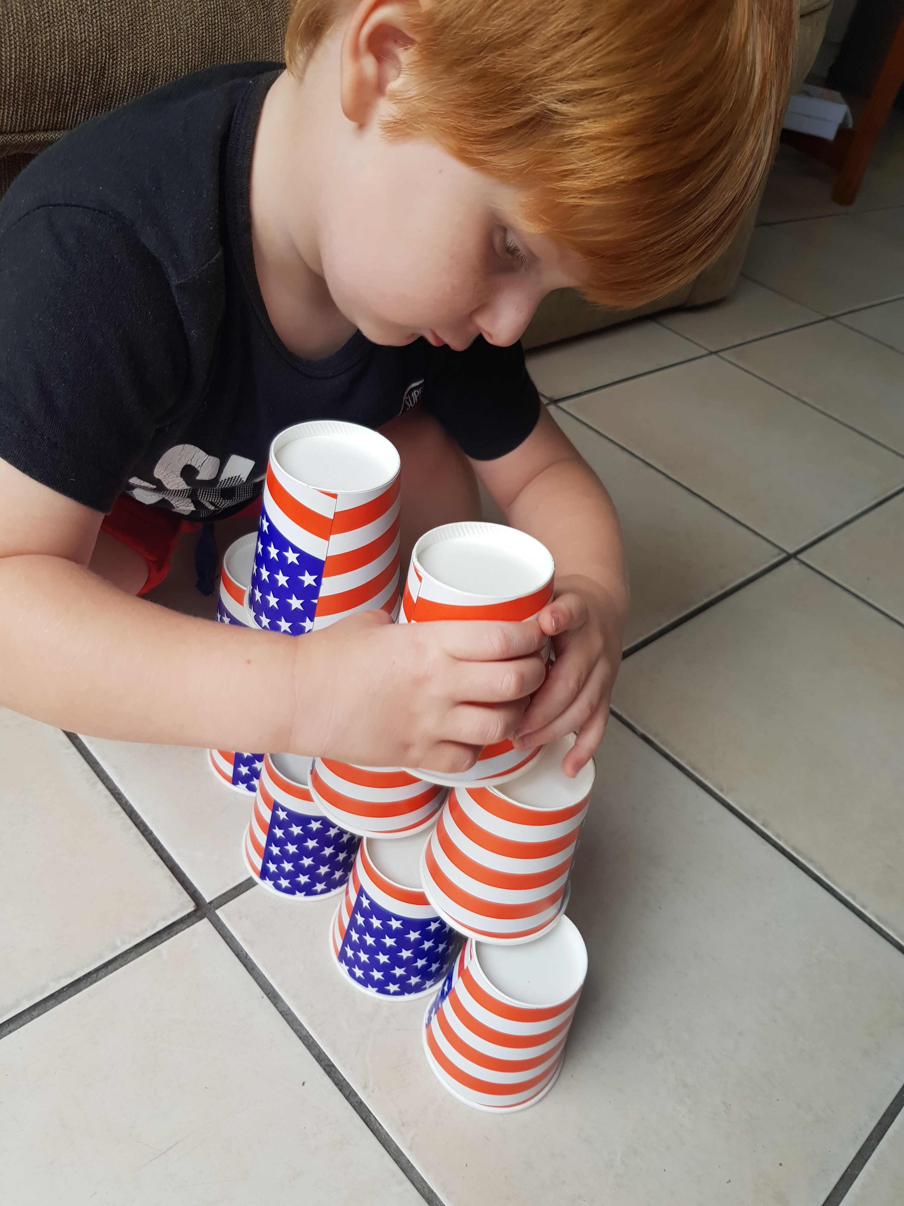 A boy stacking cups